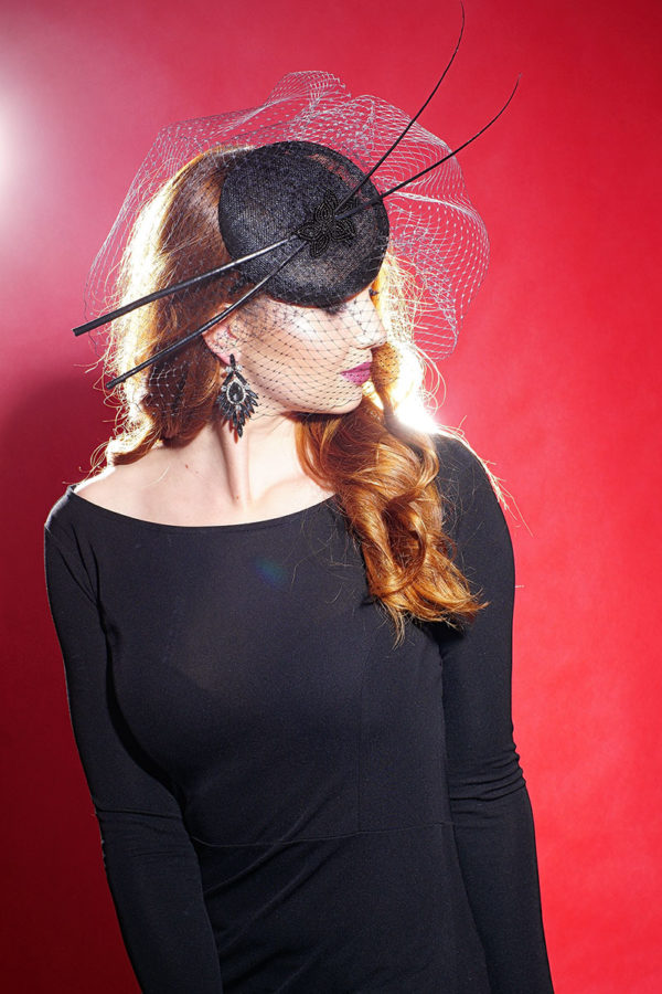 a fascinator for halloween with feathers and a veil
